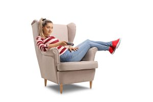 Young woman seated in an armchair watching TV isolated on white background
